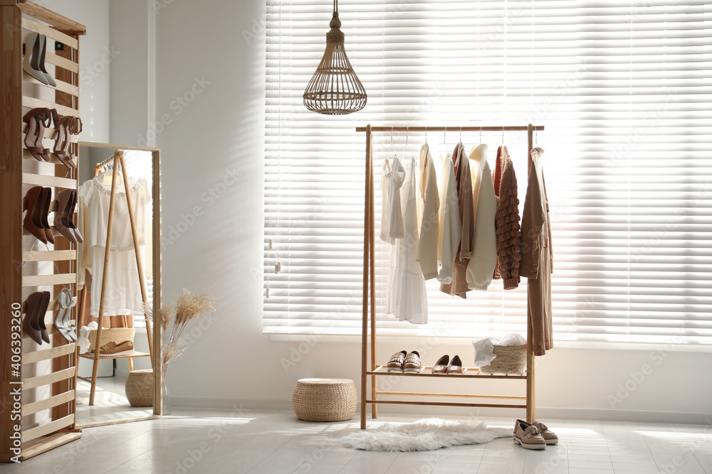 Fototapeta Modern dressing room interior with racks of stylish women's clothes and shoes