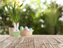Empty Wooden Surface And Wicker Basket With Colorful Easter Eggs On Background
