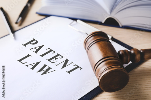 Canvas Print Clipboard with phrase Patent Law and gavel on wooden table, closeup