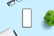 Leinwandbild Motiv Phone mockup on blue office desk. Minimal composition with plant, pad, pen and glasses