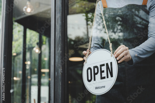 Fotografering asian waitress staff woman wearing apron turning open sign board on glass door i