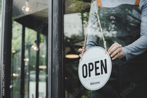 Foto asian waitress staff woman wearing apron turning open sign board on glass door i