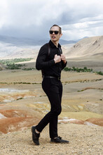 Man Model In Sunglasses And Black Clothes Posing Against The Backdrop Of The Desert Mountains