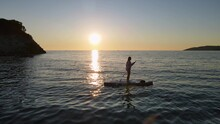 Silhouette Of Woman Rowing SUP-board With Paddle Along Sea With Rippling Waves Against Clear Sky At Sunset Reflecting On Water
