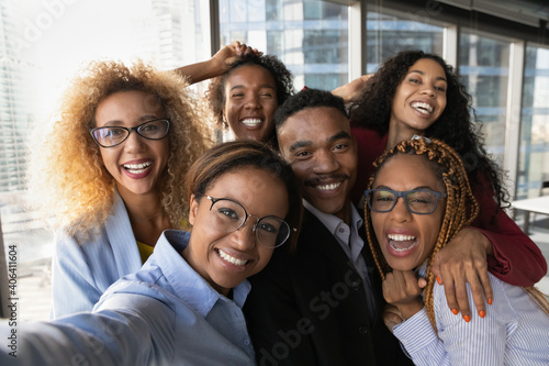 Fototapeta Close up portrait of overjoyed young multiracial employees team have fun posing for selfie on smartphone in office together