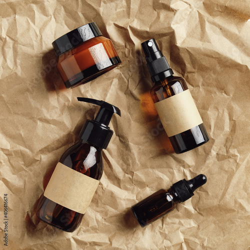 Cosmetic dark amber glass bottles on kraft paper. SPA natural organic beauty products packaging design. Flat lay, top view.