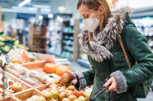 Tableau sur Toile Woman wearing ffp2 face mask shopping in supermarket