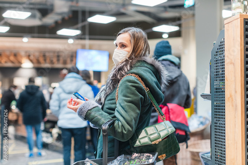 Stampa su Tela Woman standing in queue at cash desk in supermarket wearing mask