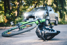 Close-up Of A Bicycling Helmet Fallen On The Asphalt Next To A Bicycle After Car Accident On The Road. Conceptual Of Accident Car Crash With Bicycle On Road.
