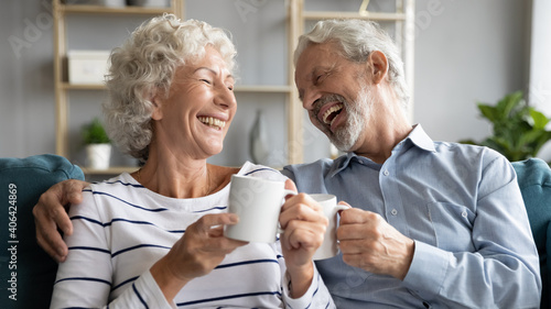 Obraz Overjoyed middle aged retired married couple relaxing on comfortable sofa, enjoying communicating while drinking hot morning coffee together at home, laughing at funny joke, family relations concept. - fototapety do salonu