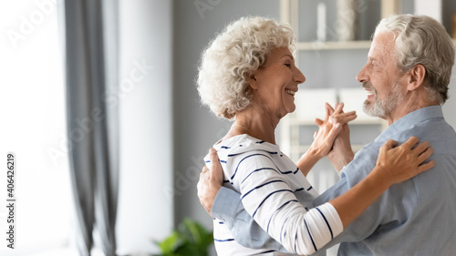 Happy romantic middle aged older retired family couple dancing slowly to favorite music, enjoying home dating or celebrating wedding anniversary together, showing love devotion and care, copy space Fototapete