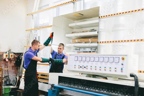 Canvas Glazier worker operates mirror glass cutting machine in workshop