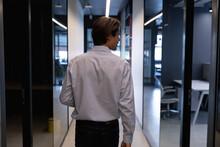 Caucasian Businessman Walking Holding A Laptop In A Modern Office