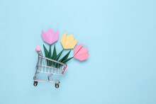 Origami Tulips Flower In Mini Shopping Cart On Blue Background.