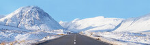 Buachaille Etive Mor And Empty Road Covered In Snow During Winter