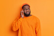canvas print picture - Serious bearded Afro American man has phone conversation talks via smartphone and looks thoughtfully aside wears hat and casual sweater poses against orange background. Communication concept