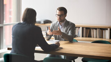 Serious Businessman Discussing Contract Details Or Finding Problem Solution With Skilled Financial Advisor In Modern Office. Two Successful Male Partners Negotiation Project Ideas In Boardroom.