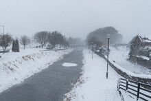 Scenery Of Frozen Canal And Walk Paths And Railways On Right.