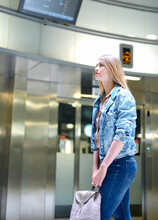 Girl With Long Hair Looks Train Schedule In The Subway. High Quality Photo