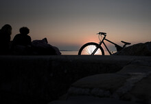 Bicycle Resting On The Rocks In Front Of The Sunset Over The Sea