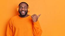Studio Shot Of Joyful Bearded Black Man Listens Audio Track Via Wireless Headphones Wears Bright Orange Long Sleeved Jumper In One Tone With Background Points Thumb Away Advertises Copy Space