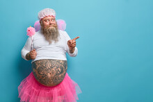 Surprised Bearded Man With Fat Tattoed Belly Wears Fairy Costume Holds Magic Wand Indicates Away With Interest Shows Something For Your Party Or Holiday Isolated On Blue Background For Your Promotion