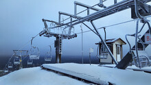 A Frozen And Abandoned Chairlift In The Snowy Mountains. A Devastated Ska Lift Covered With Snow And Frost.