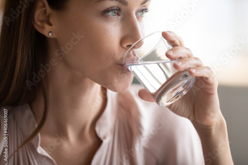 Close up attractive woman drinking pure fresh mineral water, preventing dehydration, young female holding glass, healthy lifestyle and good daily habit concept, natural beauty, skin and health care © fizkes