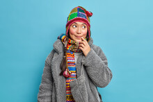 Horizontal Shot Of Thoughtful Asian Woman With Pigtail Wears Knitted Hat Wrapped Scarf Around Neck Dressed In Fur Coat Isolated Over Blue Background. People Winter Time And Thoughts Concept.