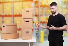 Encoding Of Products. A Man With A Barcode Reader And A Smartphone. The Storekeeper Reads Information From Cardboard Boxes. Marking Of Goods.
