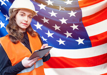 A Girl In A White Helmet With A Tablet In Her Hands Against The Background Of The American Flag. Search For Jobs In The United States. Work In America. Jobs For Engineers In The United States.