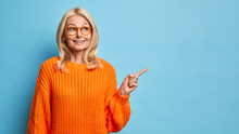 Thoughtful Blonde Forty Years Old European Woman Wears Spectacles And Knitted Orange Sweater Points Away On Blank Copy Space Shows Place For Your Advertisement Isolated Over Blue Background.