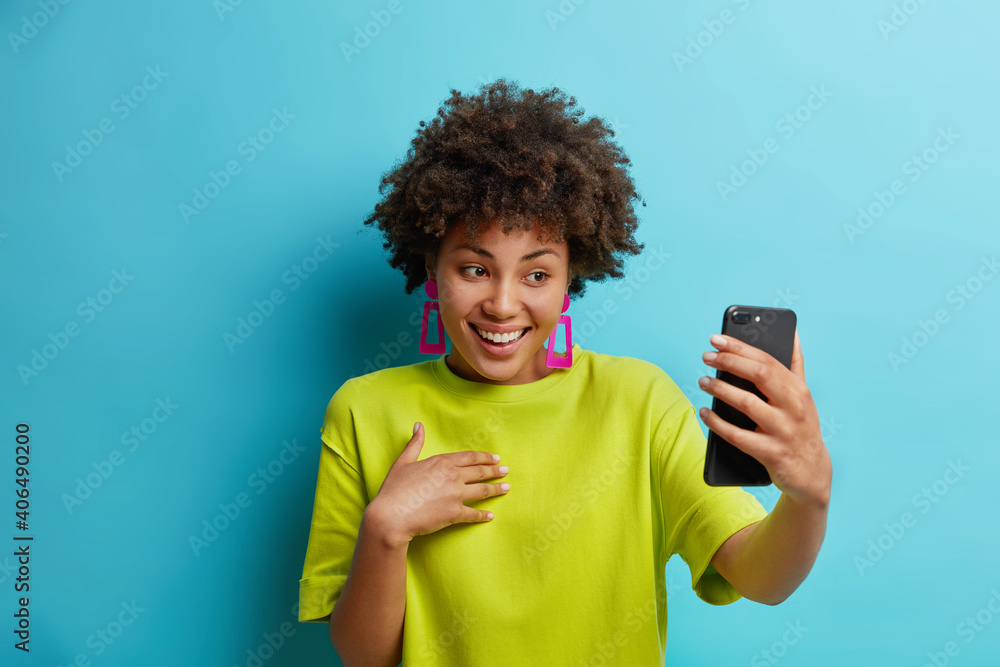 Fototapeta Pretty young African American woman holds modern mobile phone in front of herself has online conference makes video call connected to wireless internet enjoys positive talk wears green t shirt
