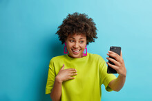 Pretty Young African American Woman Holds Modern Mobile Phone In Front Of Herself Has Online Conference Makes Video Call Connected To Wireless Internet Enjoys Positive Talk Wears Green T Shirt