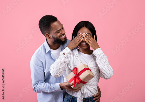 Fotografie, Obraz Caring African American man covering his girlfriend's eyes and surprising her wi