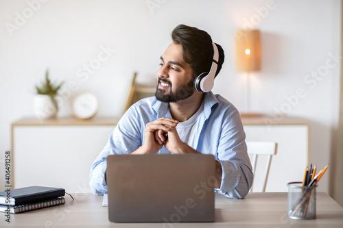 Obraz Smiling arab man in headphones listening music while working on laptop - fototapety do salonu