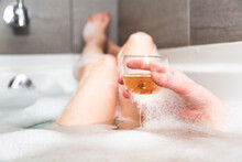 Closeup Of Woman's Hand Holding A Glass Of White Wine While Taking A Nice Warm Bubble Bath In An Hotel Room. Concept About Lifestyle, Travel, Relaxation And People.