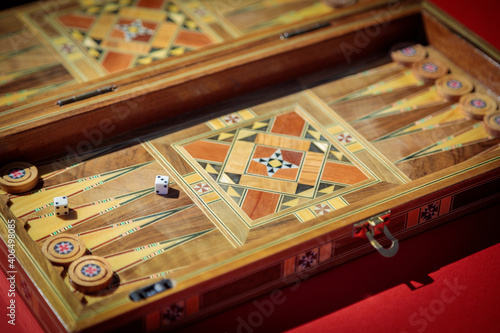 Fotomural An entertaining game of backgammon on a red background