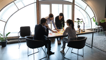 Diverse employees working with project documents, using sticky papers, writing notes, colleagues developing business project strategy, marketing plan, analyzing charts and diagrams in modern office