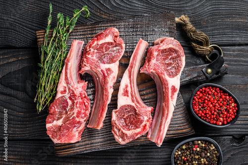Fotografia Lamb chops raw meat on bone with salt, pepper and herbs