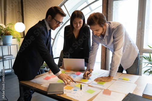 Diverse colleagues working with financial documents, writing notes on colorful stickers, project statistics in office, Indian businesswoman with coworkers developing business strategy, teamwork