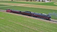 Aerial View Of A Restored Antique Steam Locomotive Pulling A Caboose On A Sunny Fall Day