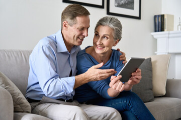 Fototapeta Boks Happy older mature couple using digital tablet sitting on sofa at home. Smiling senior retired family 60s husband and wife holding pad enjoying modern technology shopping or banking online together.