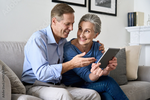 Happy older mature couple using digital tablet sitting on sofa at home. Smiling senior retired family 60s husband and wife holding pad enjoying modern technology shopping or banking online together.