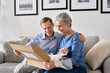 canvas print picture - Happy older mature couple customers unpacking parcel sitting at home on couch. Senior middle aged grandparents opening online store order receiving gift in postal delivery shipping box.