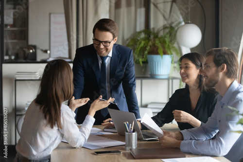 Smiling team leader with employees listening to businesswoman at corporate meeting, sitting in modern boardroom, happy colleagues partners discussing project strategy, sharing startup ideas