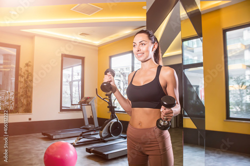 Obraz A beautiful athletic young brunette woman in sportswear in the gym. Healthy lifestyle. - fototapety do salonu