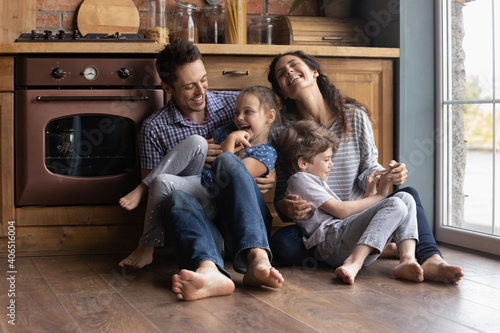 Excited young Caucasian parents sit on warm floor relax in kitchen have fun tickle happy small kids. Overjoyed family with two little children relax play on leisure weekend in new own home together.