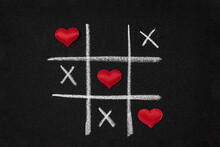 Red Hearts And Tic-tac-toe On Black Grainy Cardboard. Love Game Concept.