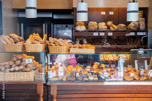 Interior of small Spanish bakery shop with racks and showcase full of pastries a Fototapeta
